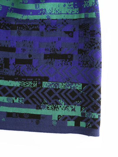 Glitch scarf with a knitted glitched pattern inspired by Art deco design style. It's knitted in extra fine Italian merino wool. Glitch textile design close up in blue and green colours.