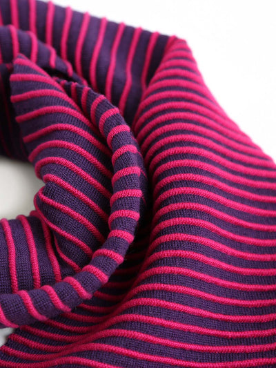 Our soft merino wool scarf has a unique texture with a gradient of knitted ribs. Detail of a Hot pink & purple knitted scarf.