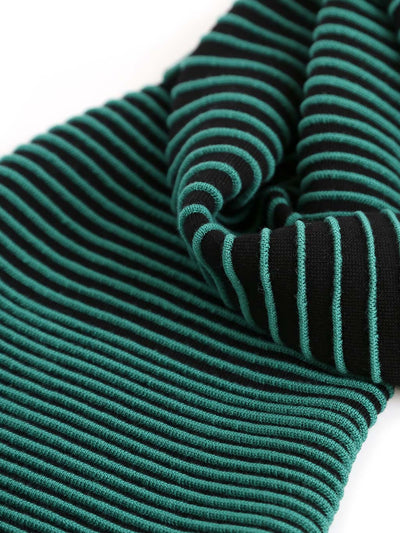 Our soft merino wool scarf has a unique texture with a gradient of knitted ribs. Detail of a black and green knitted scarf.