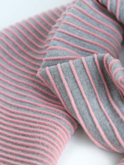 Our soft merino wool scarf has a unique texture with a gradient of knitted ribs. Detail of a pink and grey knitted scarf.