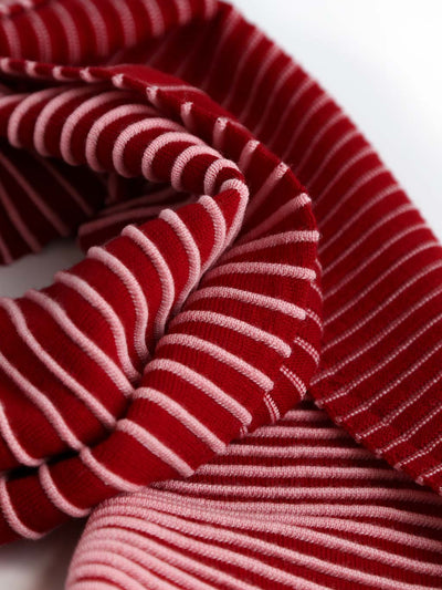 Our soft merino wool scarf has a unique texture with a gradient of knitted ribs. Detail of a pink and cherry knitted scarf.
