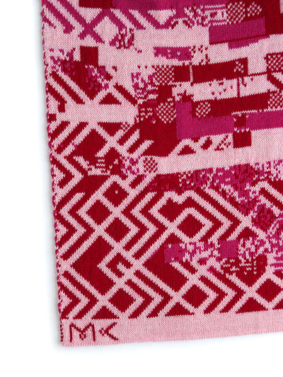 Glitch scarf with a knitted glitched pattern inspired by Art deco design style. It's knitted in extra fine Italian merino wool. Glitch textile design close up in red and pink colours.