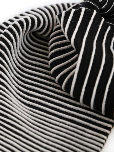 Our soft merino wool scarf has a unique texture with a gradient of knitted ribs. A detail of a black and white knitted scarf.