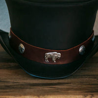 close up on big buffalo hatband on the coachman top hat