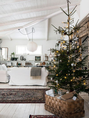 Rustic white living room interior with shelves, white sofa and a sparse Christmas tree