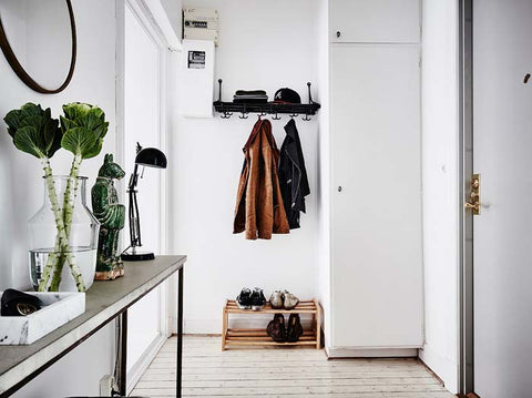 Entry way with a console table, coat racks and a cabinet