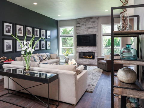 Modern living room with dark green wall, wooden floor, cream sofa and fireplace
