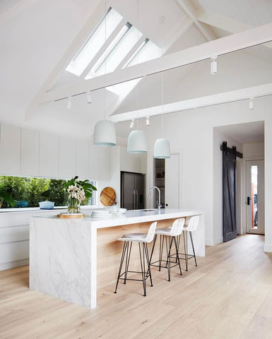 White modern kitchen with marble benchtop, 3 pandant lights and 3 rattan barstools