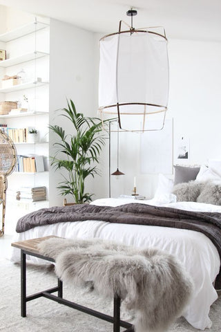 White bedroom with a big hanging lamp and a plant in a Scandinavian home