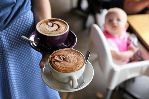 Waitress holding two cups of coffee with baby in the background