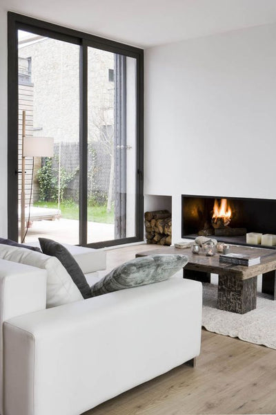 Living room with white sofa, floor to ceiling windows and a fireplace