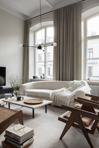 Minimalist interior with white sofa, brown chairs and cream curtains