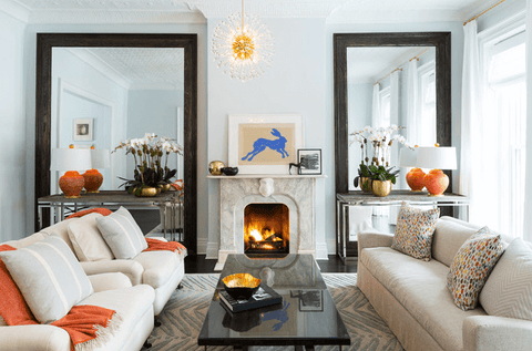 Living room with two big mirrors, orange throw and lamps