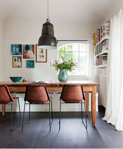 Dining room with mix and match furniture, wall mounted bookshelves, paintings on the wall and random decorations