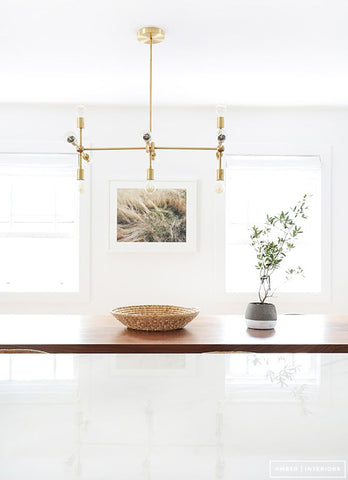 White dining interior with gold light, painting on wall, rattan basket and concrete vase on table.