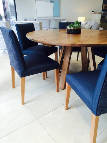 Round hardwood Maison dining table with navy blue upholstered chairs