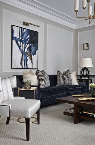 Navy blue velvet sofa in a formal sitting room with a white occasional chair