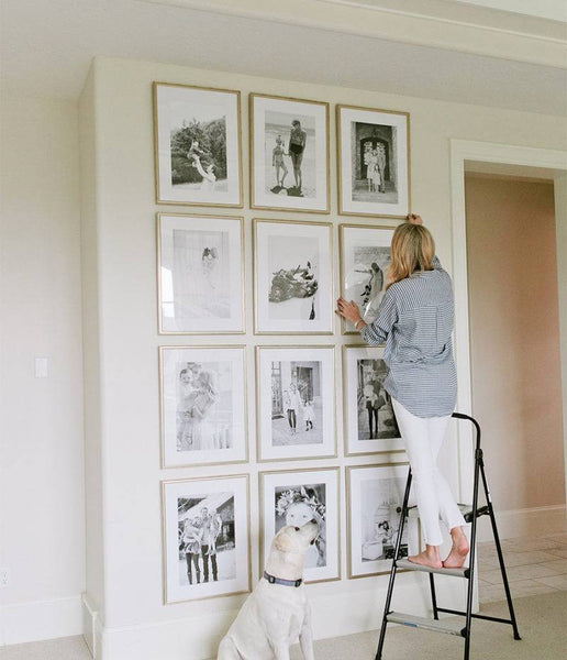 Woman hanging framed photos in wall to ceiling grid gallery style.