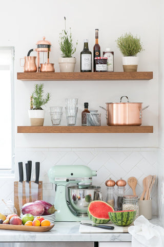 Timber floating shelves on a white kitchen wall with a variety of practical and aesthetically pleasing items including pot-plants and matching copper kitchen items.