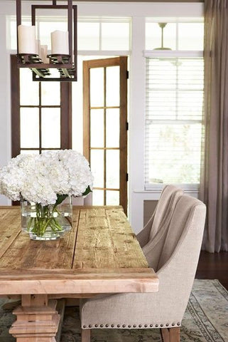 Dining table with fresh cut hydrangea flowers in a glass vase on top.