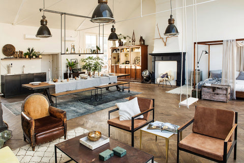 Eclectic Interior With Black Industrial Lights, Brown Leather Armchairs, A  Swing, Long Dinning