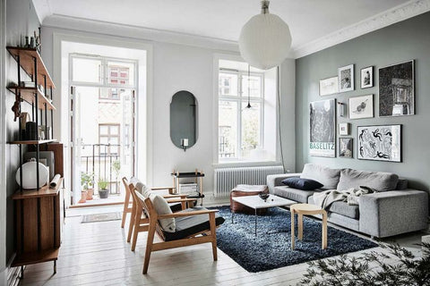 Scandinavian apartment living room interior with greyish green walls, black carpet, wooden armchairs, grey sofa, oval mirror and a round white light