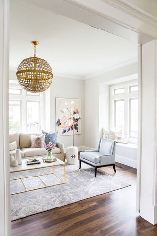 White living room interior decor with cream sofa, light blue chair and globe pendant light