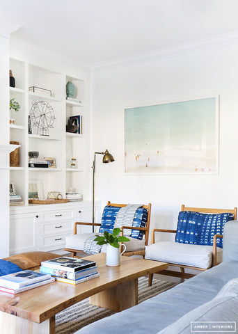 White living room interior with blue cushions, light bluish grey sofa, white cabinets and wooden coffee table