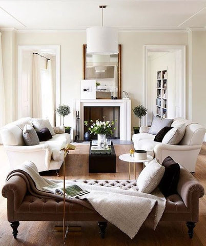 White living room interior with a fire place, white sofas and a brown day bed.