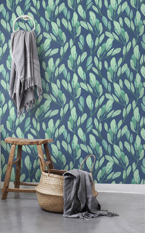 Bathroom wall with tranquil removable wall art of green leaves on a blue background.
