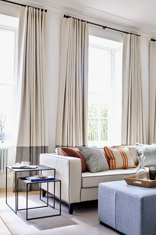 Lounge room with long neutral curtains.