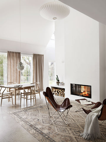 Brown leather butterfly chairs in front of fireplace