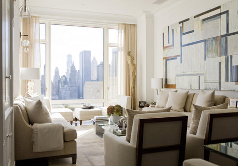 Apartment living room with white walls, cream coloured sofa, cream curtains, white table lamps and a big painting on the wall