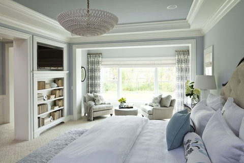 Bedroom interior with light blue walls, built-in shelf and decorative cornices