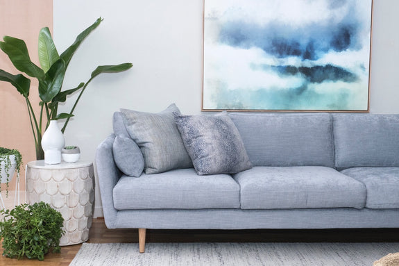 Alberto sofa styled with lush greenery, airy art, rug and side table