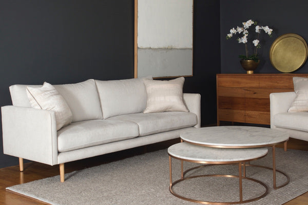 "Cream Nellie 2.5 seat sofa styled in a luxe setting with the Jarvis buffet in spotted gum, a white orchid flower arrangement, Elle marble round nested coffee tables, neutral art ""Adrift"" and taupe wooden rug"