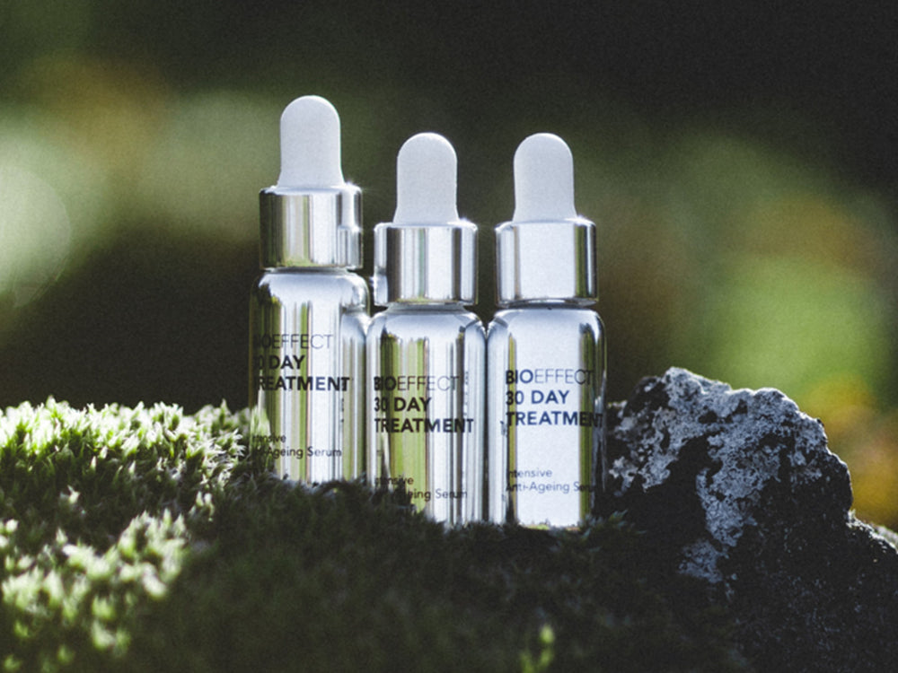 30-Day anti-aging skincare treatment products photographed on moss next to volcanic rock
