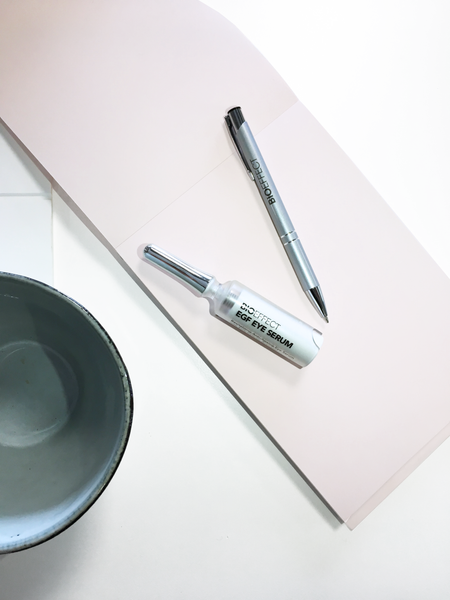 EGF Firming Eye Serum and a BIOEFFECT pen on a notepad next to a bowl