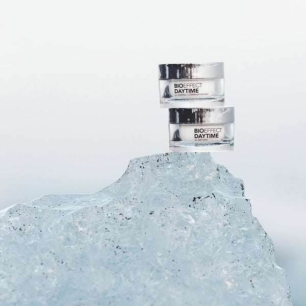 Two short, wide, cylinder-shaped jars of BIOEFFECT DayTime day cream sit at the top edge of an ice glacier.