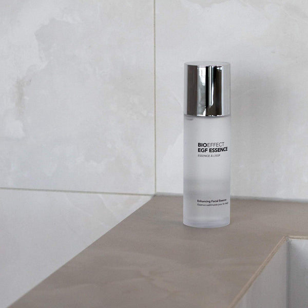 Bottle of BIOEFFECT EGF Skincare Essence sitting on a shower ledge.