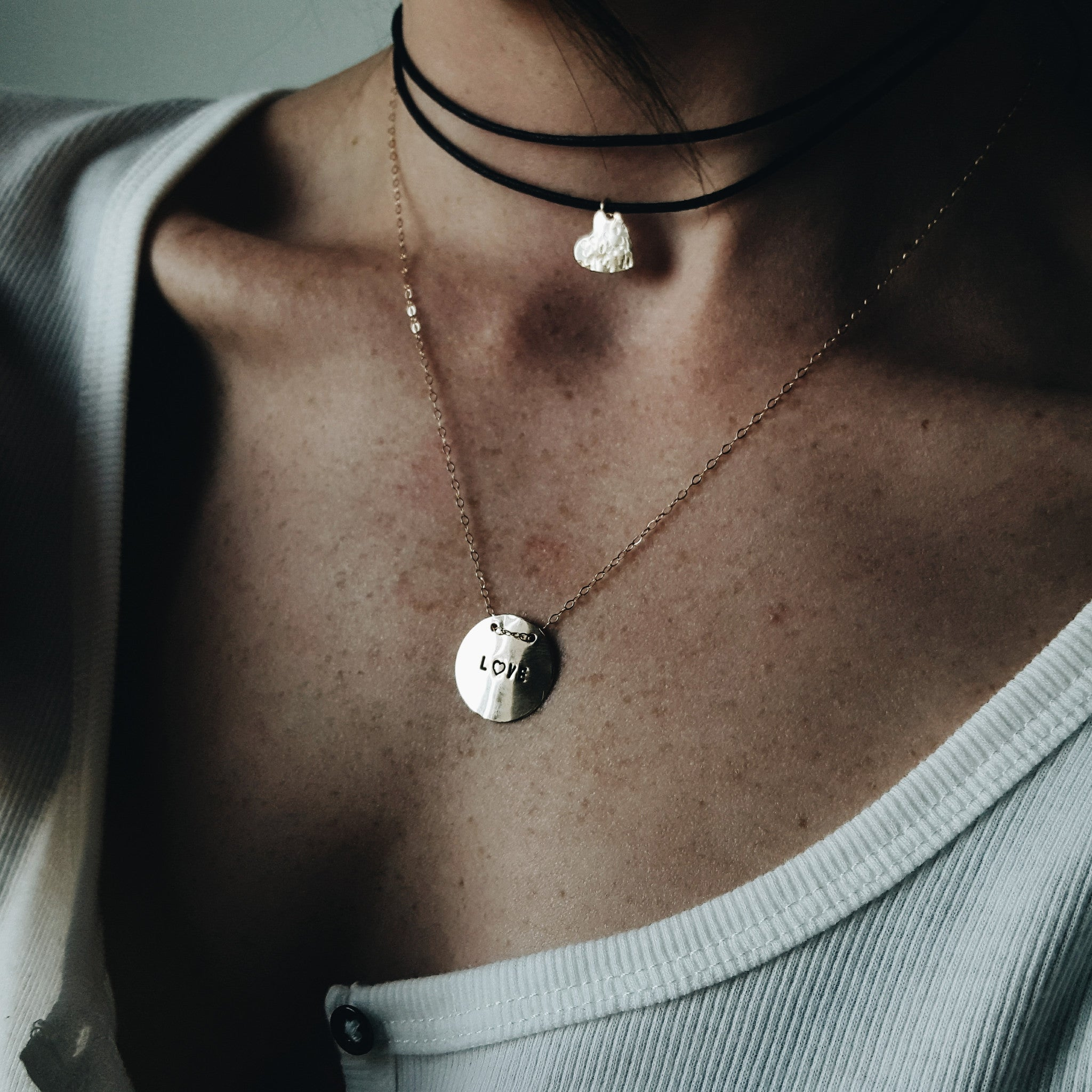 a close up of a woman's neck with a black wrapped chocker and a gold pendant with love stamped on it