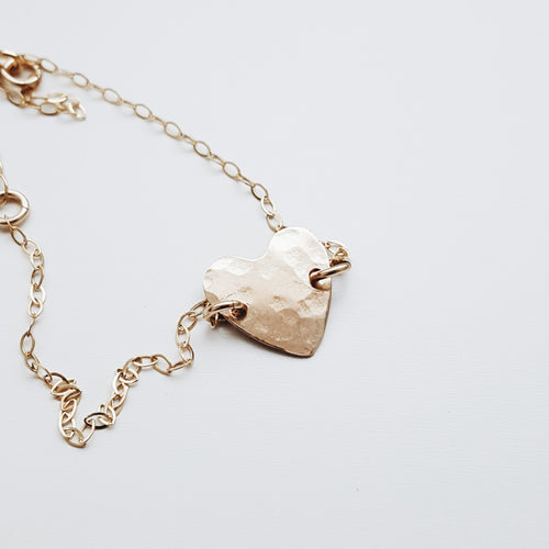 a small gold hammered metal heart on a gold chain with a white background