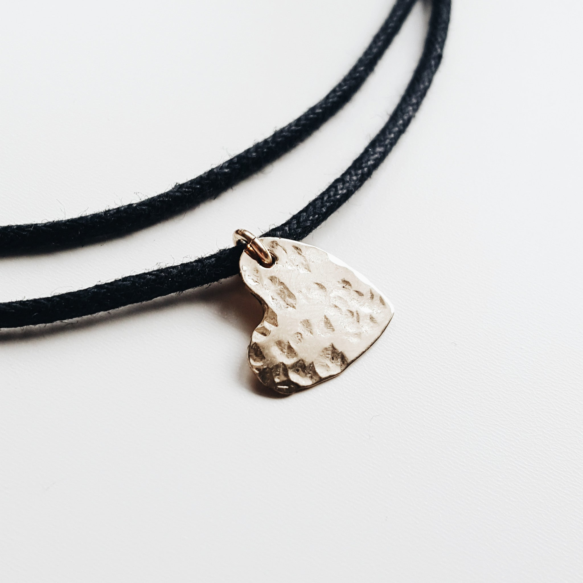 a black rope necklace with a small gold hammered heart necklace on a white background