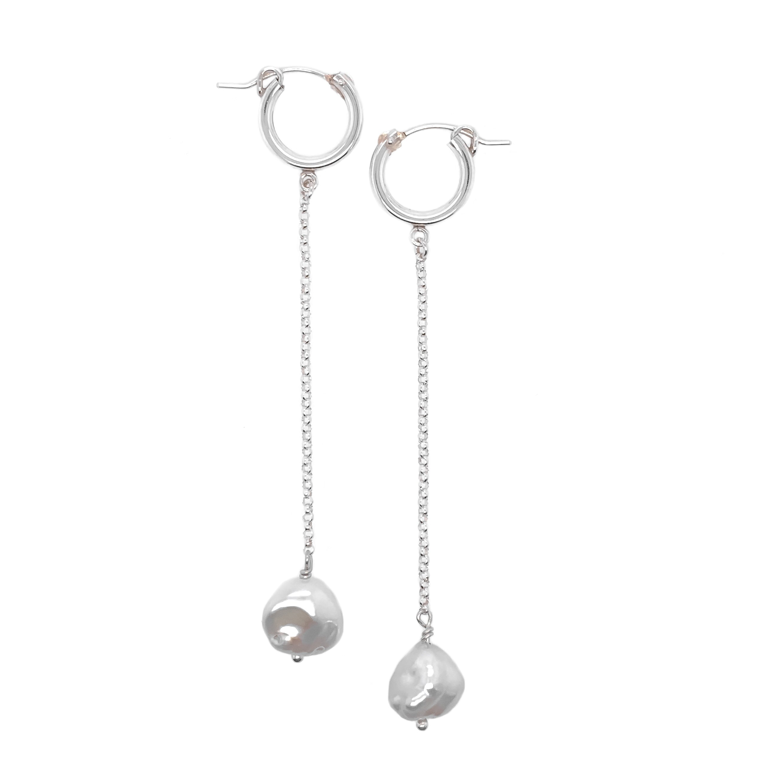 a set of dangly drop earrings with silver hoop closures, a silver drop chain and natural pearls at the bottom shown on a white background