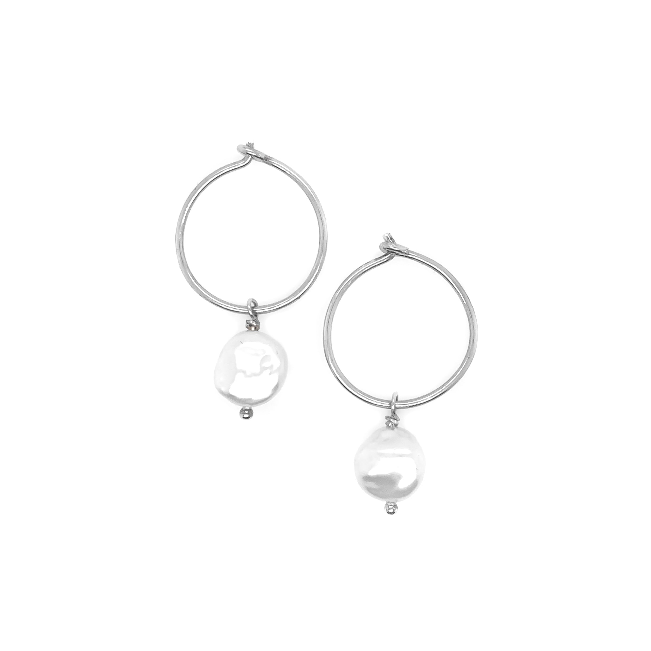 a set of small silver hoop earrings with a single pearl shown on a white background