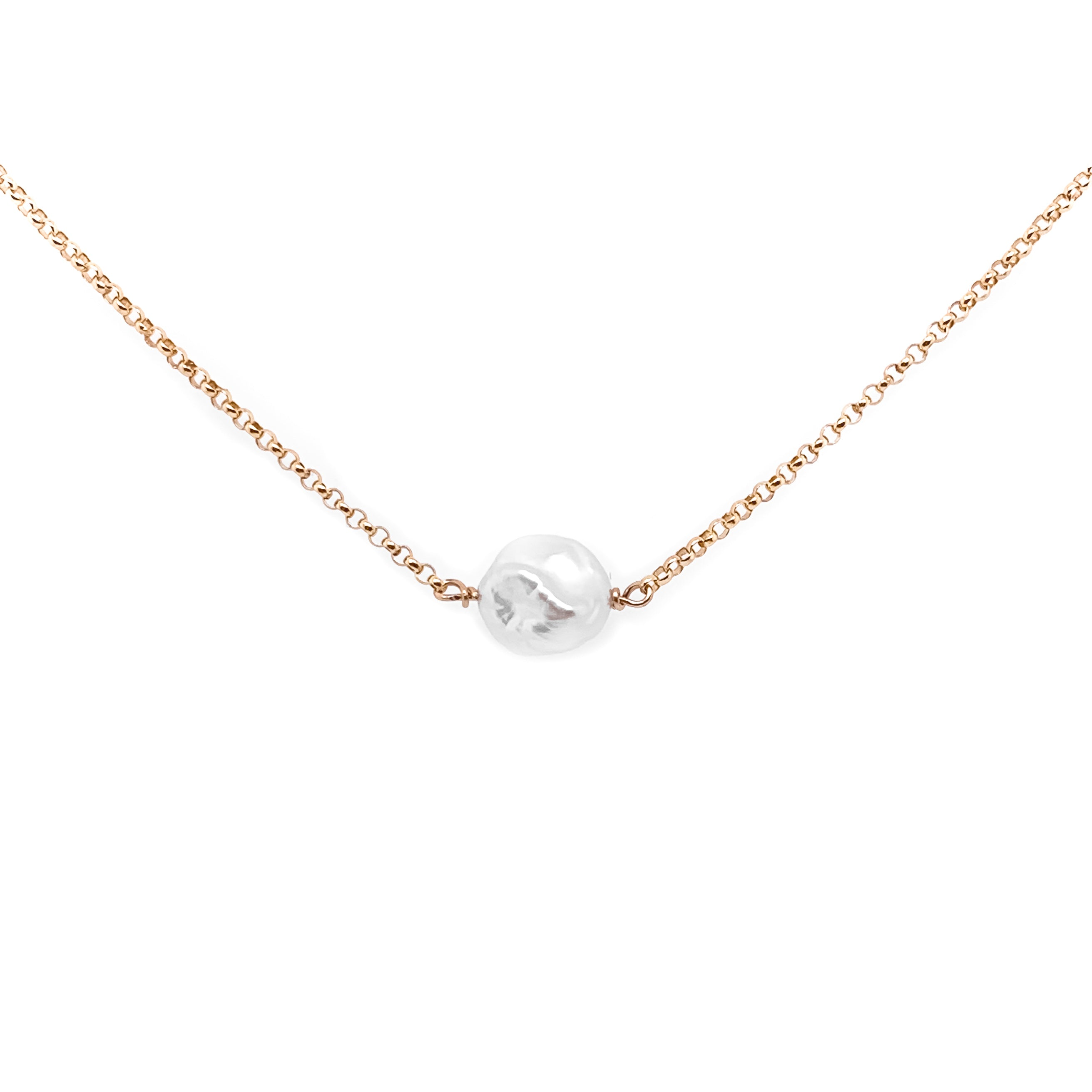 a small natural pearl with a gold chain on a white background