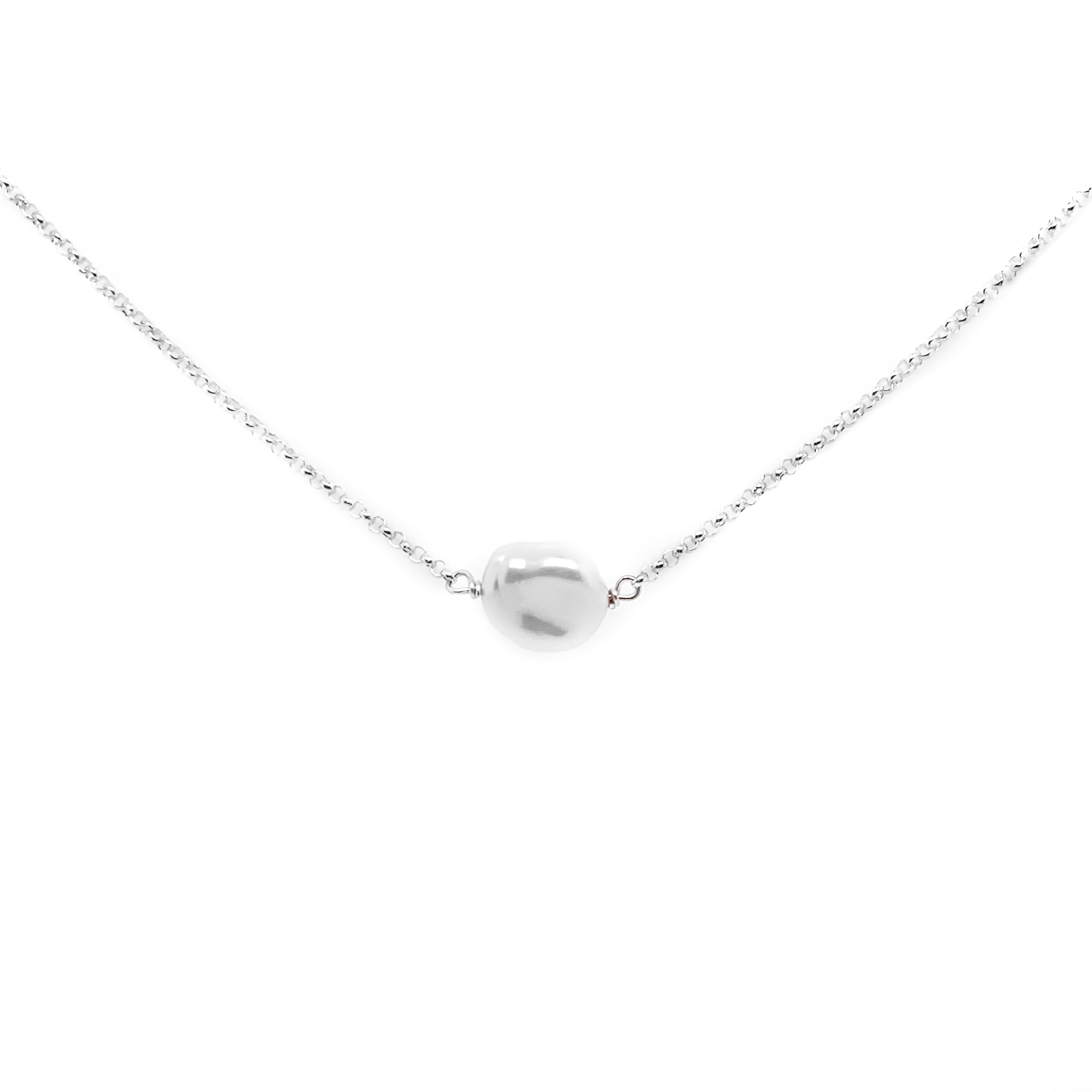 a small natural pearl on a silver chain with a white background