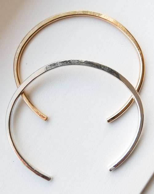two cuff bracelts, one gold and one silver on a white background