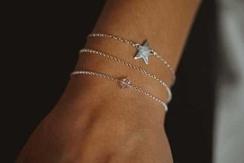 a close up of a wrist wearing a silver chain bracelet, a silver star pendant bracelet and small herkimer diamond bracelet