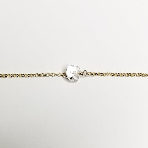 a herkimer diamond on a yellow gold chain with a white background